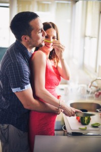Young couple cooking together in the kitchen while man embracing his pregnant wife