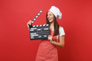 Housewife female chef cook or baker in striped apron, white t-shirt, toque chefs hat isolated on red wall background. Woman holding classic black film making clapperboard. Mock up copy space concept