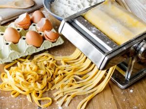 Fresh pasta cutting in machine. Fettuccini homemade.