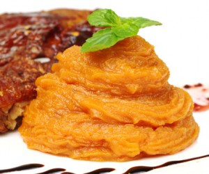 A pile of orange sweet potato puree with a mint leaf on top (Selective Focus, Focus on front of the puree and the front leaf)